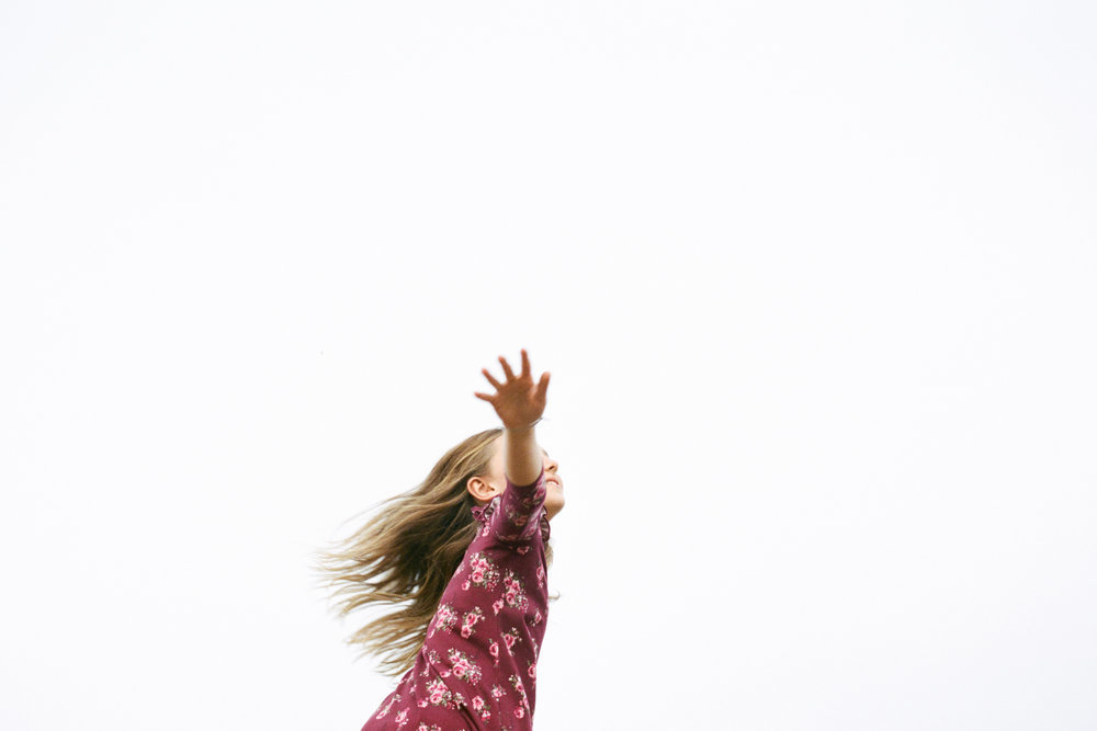young girl with outstretched arms in nature with open sky in the background