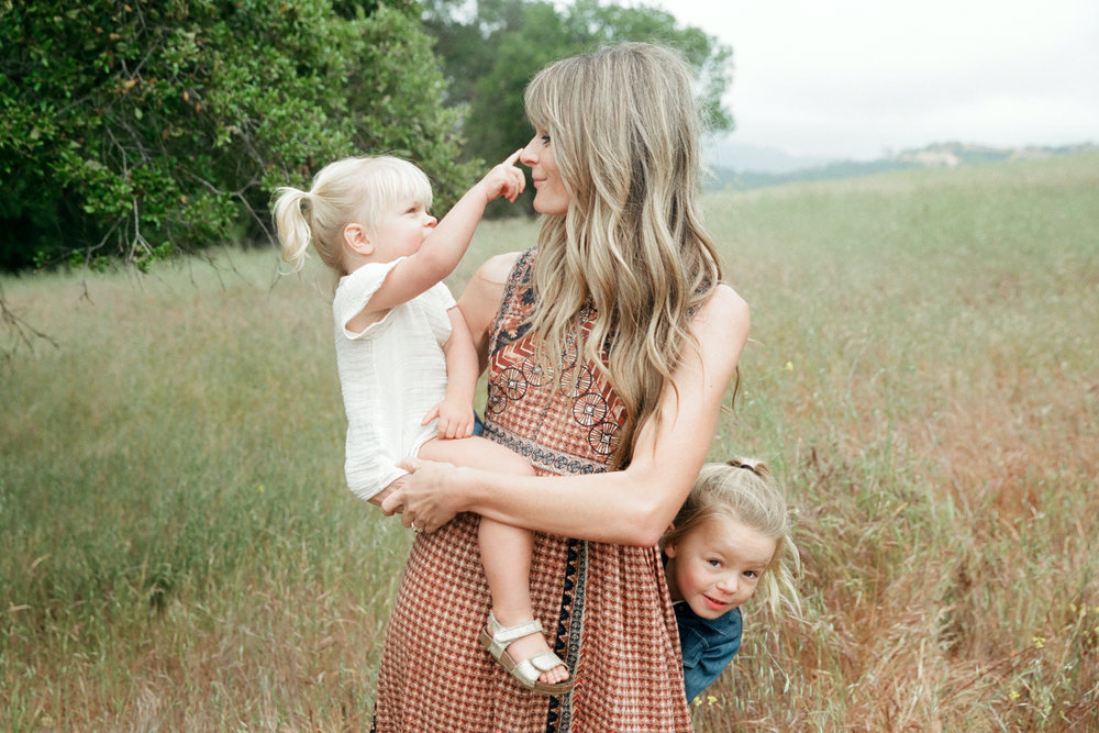 mother with two young daughter in nature playfully interacting