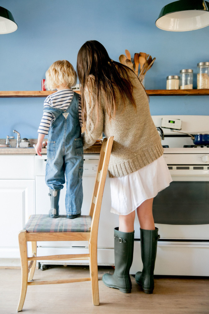 child standing on chair helping mother cook in kitchen
