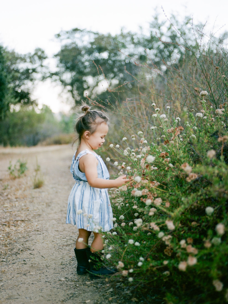 smiling young girl picking flowers on trail