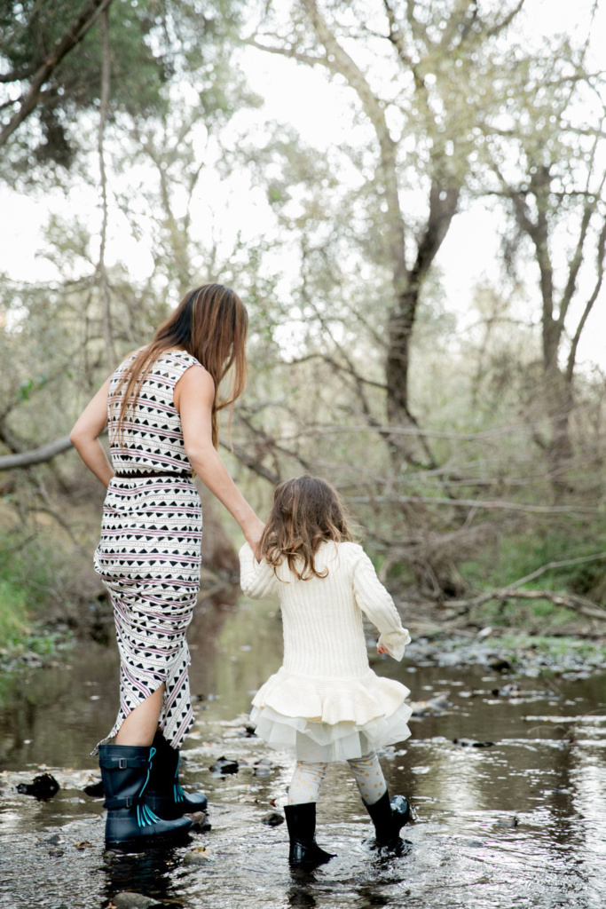 mother and young daughter walking down a creek bed with matching rubber boots