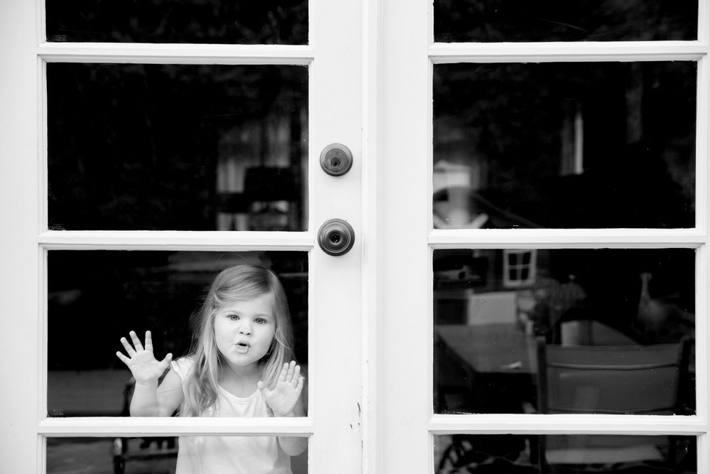 young girl pressing face up against window pane playfully