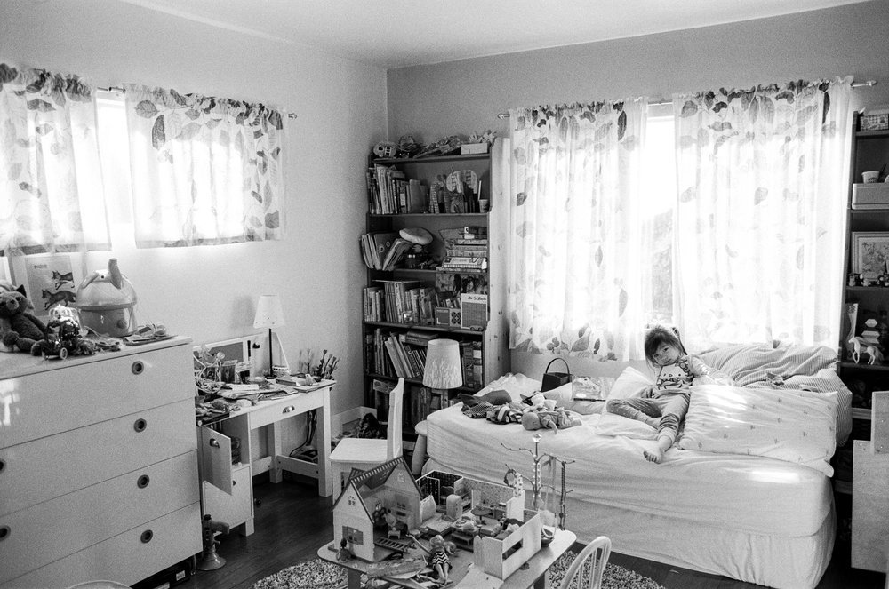 young child on bed in messy bedroom
