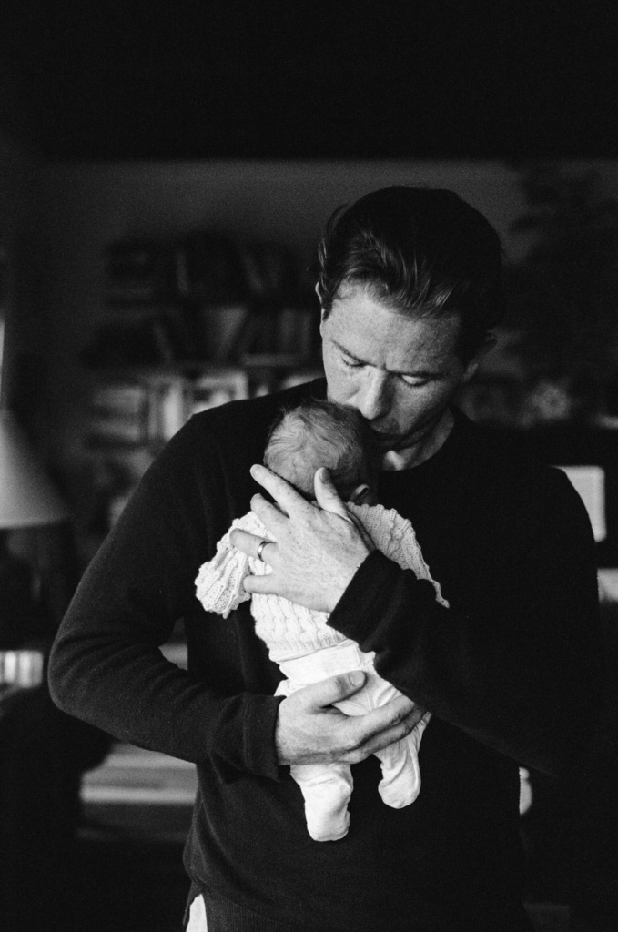 father holding and kissing a newborn son