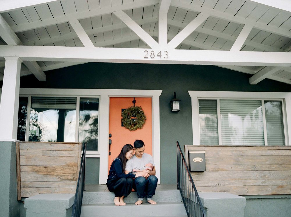 parents sitting on front porch holding newborn