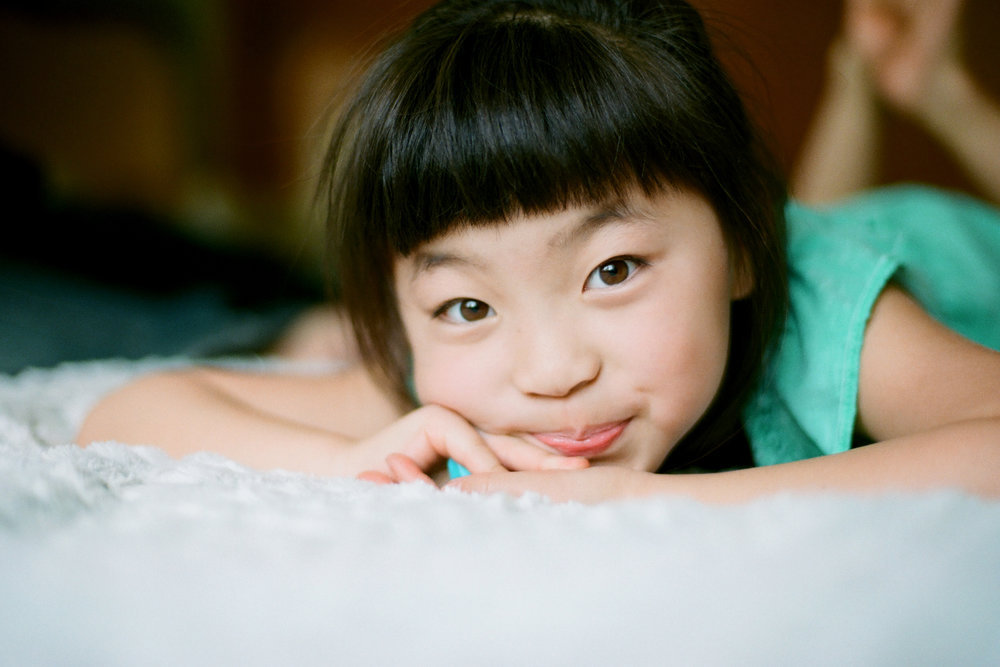 portrait of young girl laying on bed and smiling at camera