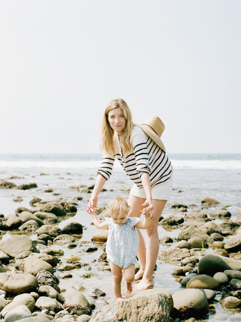 mother and young girl at the beach holding hands in a tide pool