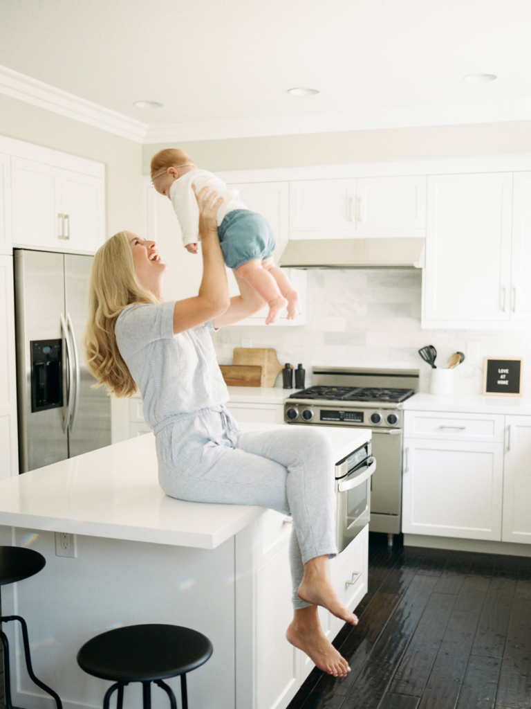 mother holding up baby and smiling on kitchen counter