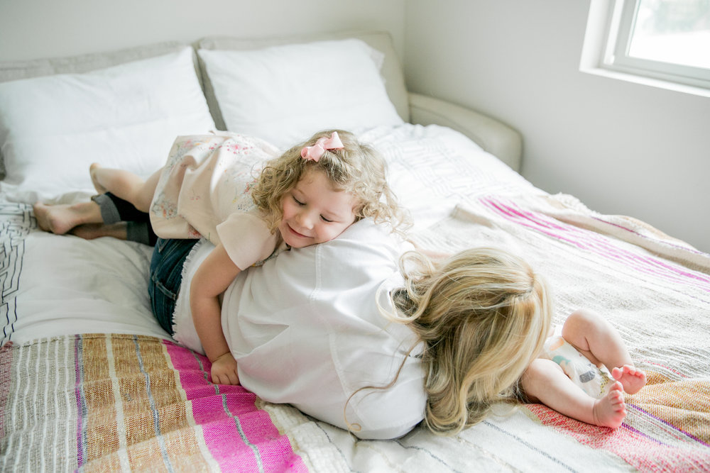 mother and two children in bed while yound girl hugs her with closed eyes