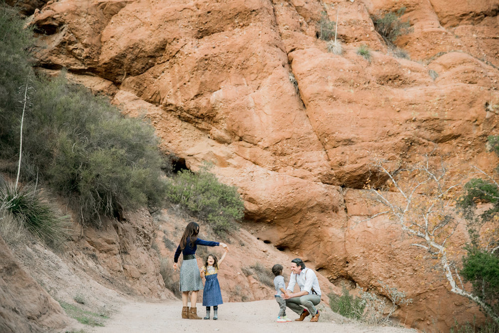 parents playing with 2 children with a background of large red rocks