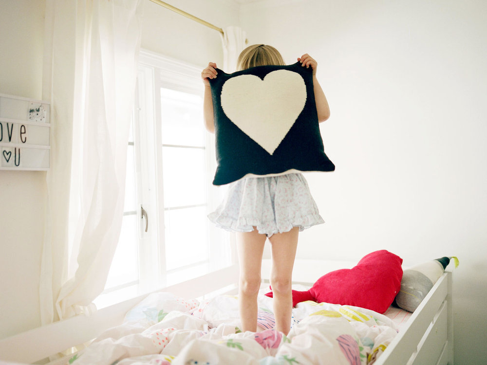 young girl standing on her bed holding heart pillow over her face playfully