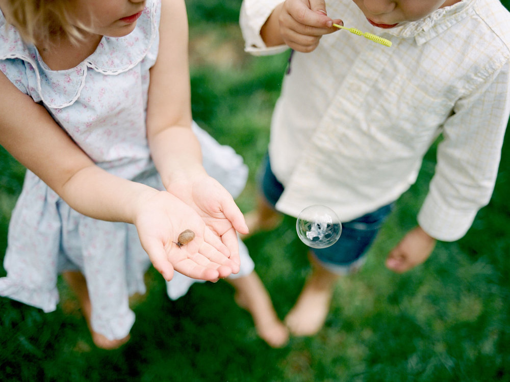 close up of two young children holding a snail and blowing bubbles