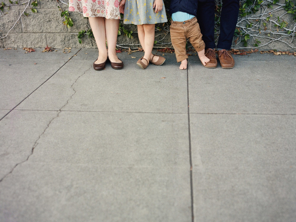 playful photo of a family of four with all focus on feet
