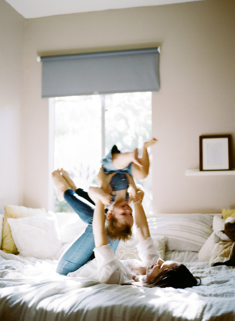 action shot of mother flipping young smiling boy while playing on a bed