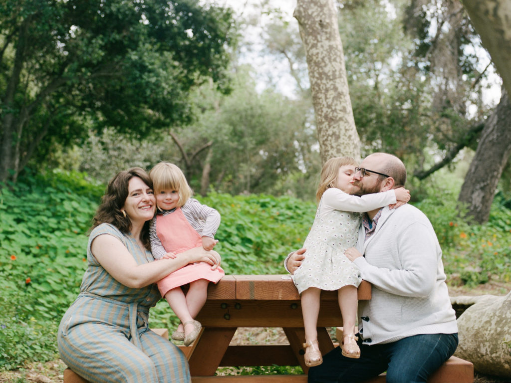 family of four interacting playfully on a picnic bench
