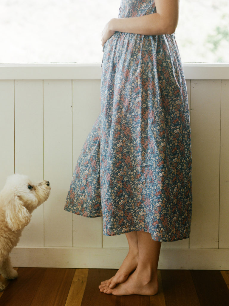 pregnant woman in vintage dress holding belly white white fluffy dog looks up at her