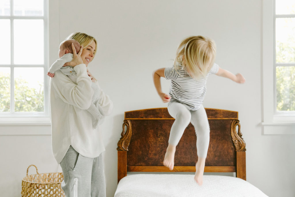 Los Angeles family photography : at home lifestyle photo of mom and newborn with big sister jumping on the bed