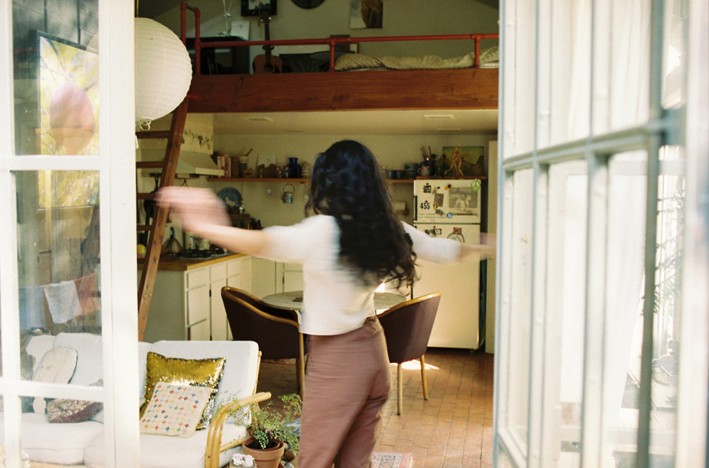 young woman spinning in house playfully