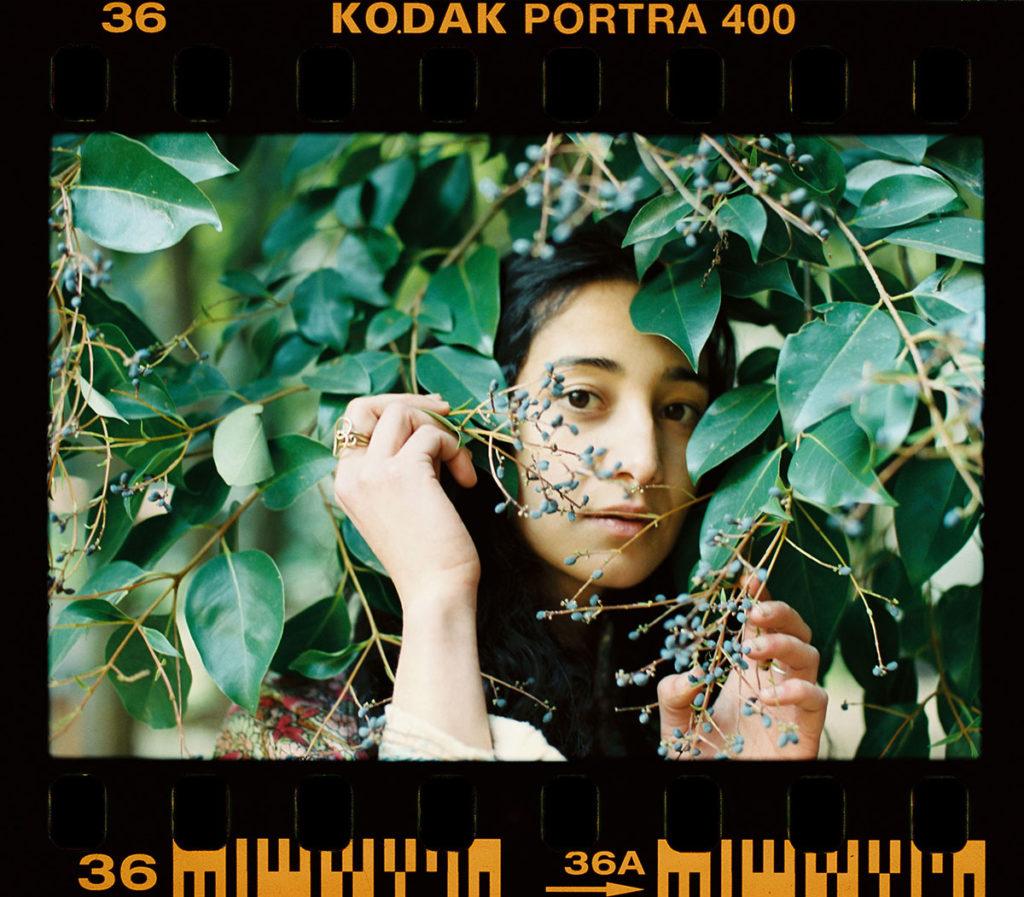 young woman behind plants looking pensivly at camera