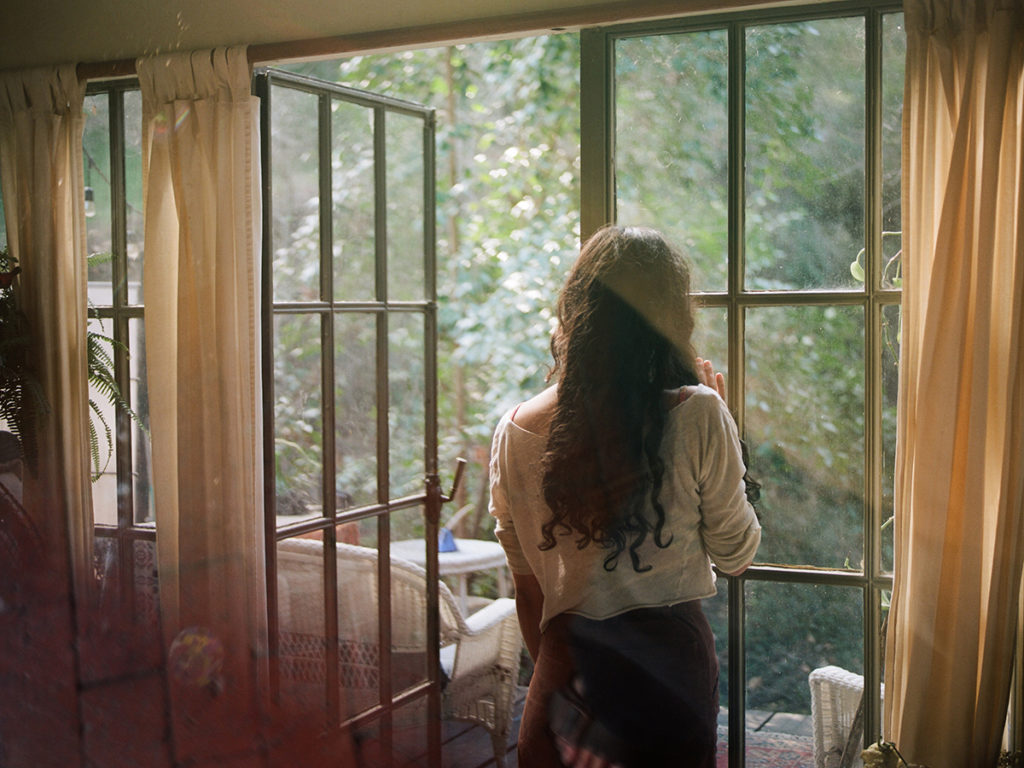 woman looking out a glass window into nature