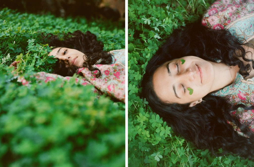 young woman laying in clovers happily