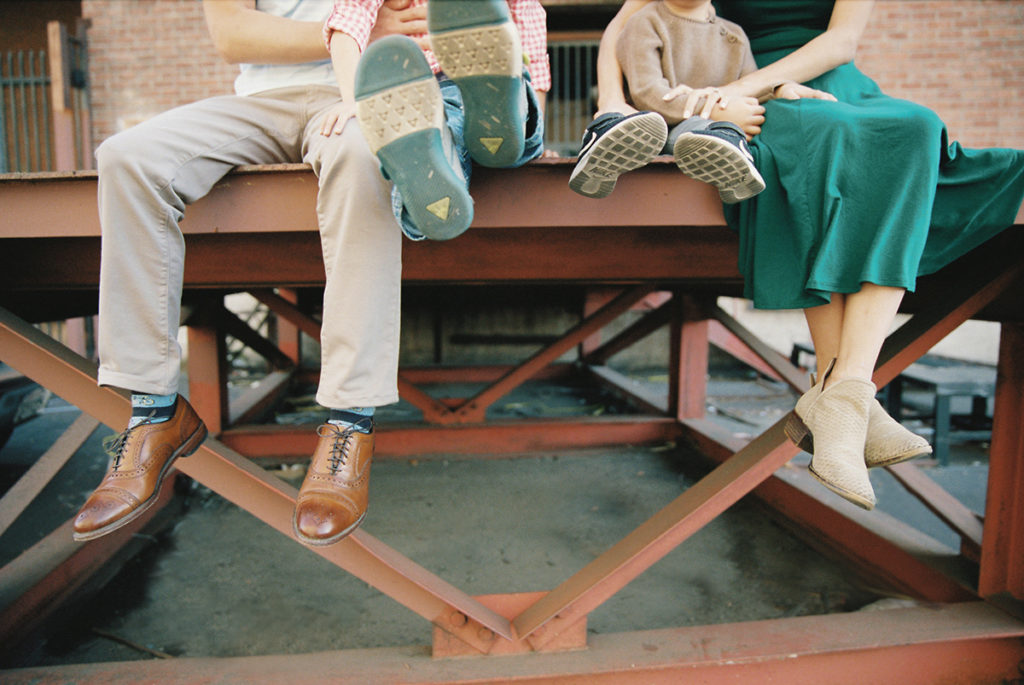 Family of 4 sitting on a metal dock with focus on feet