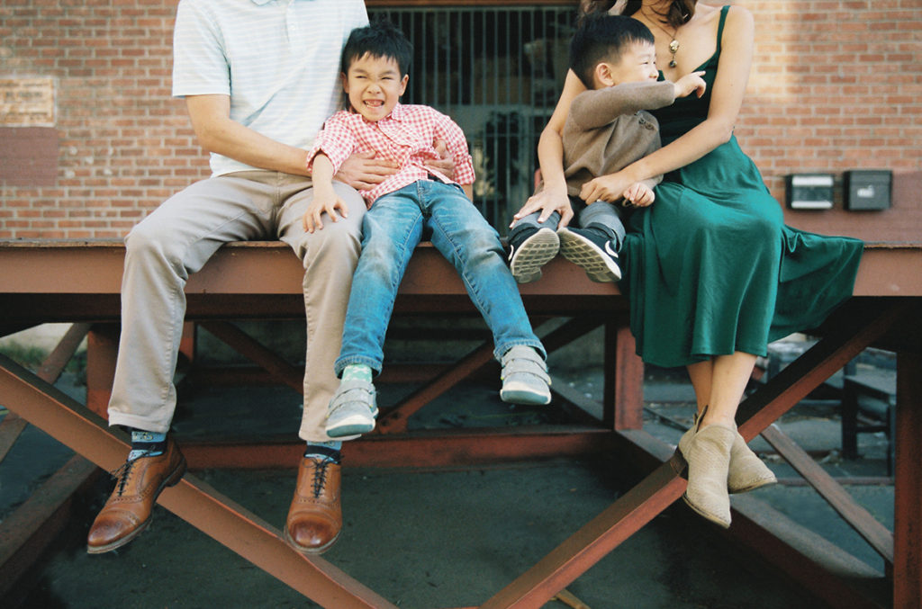 family of four sitting on a metal dock with parents tickling the children while they laugh