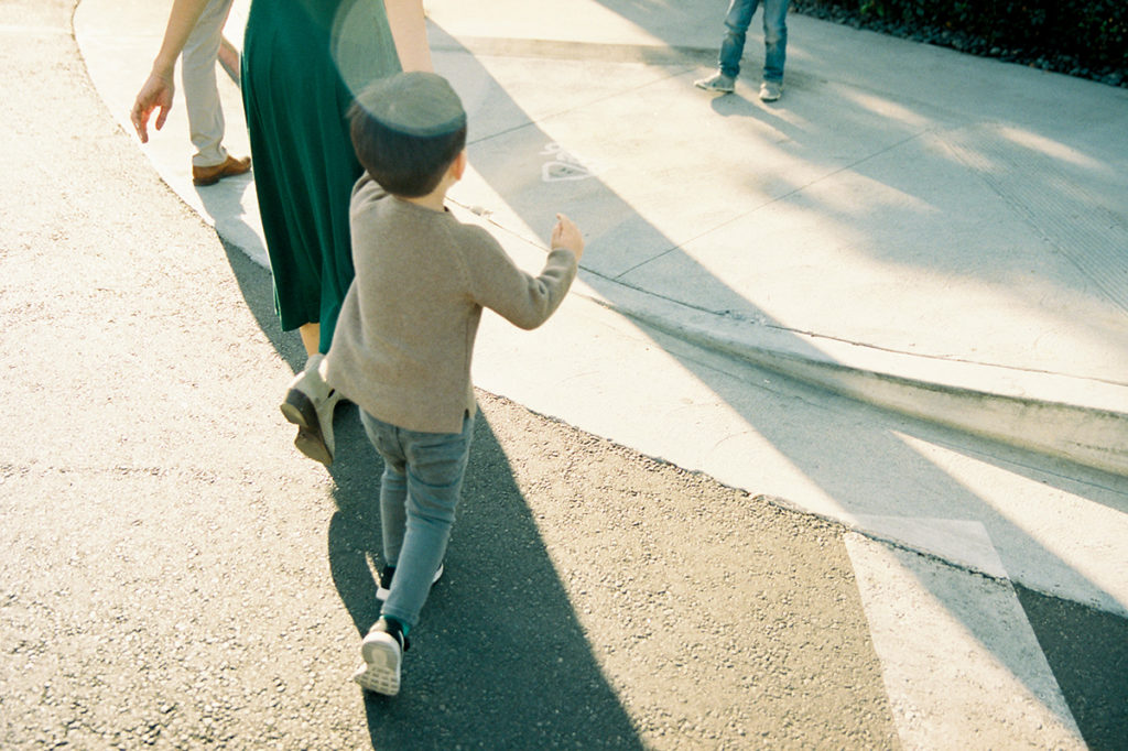 family corssing the street with focus on the littlest boy from behind holding moms hand