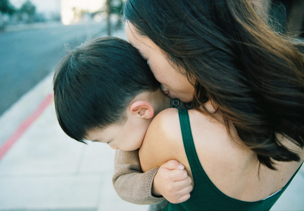 close up of mother kissing yound sons neck