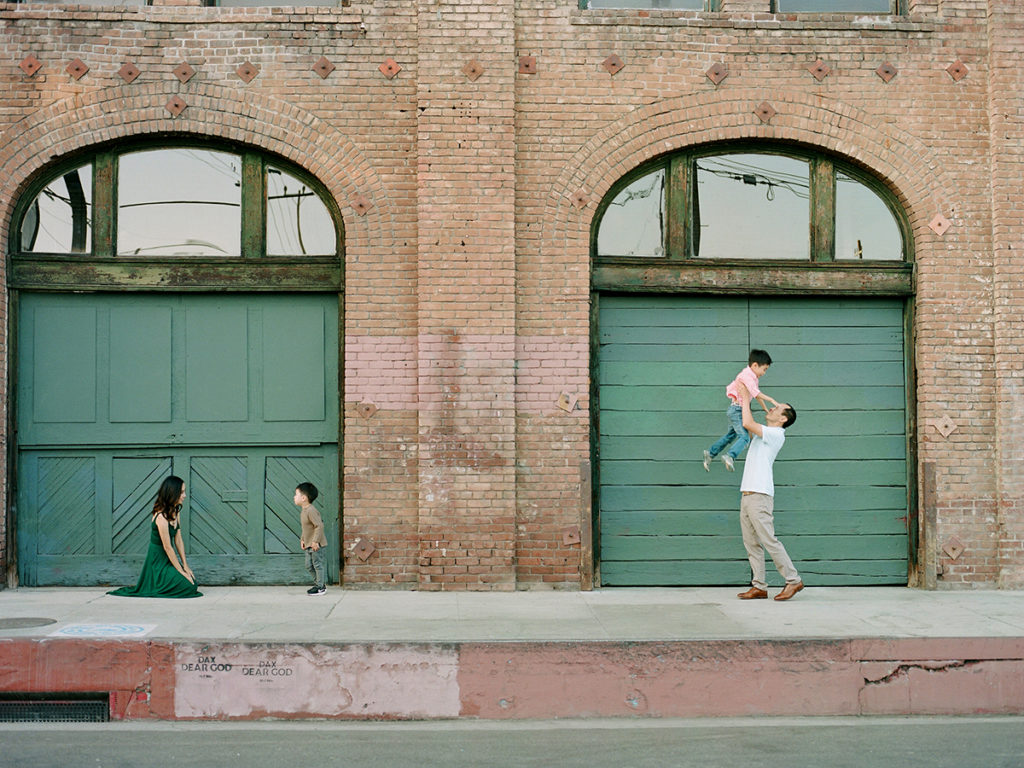 family of four with brick wall background, parents playing and interacting with kids