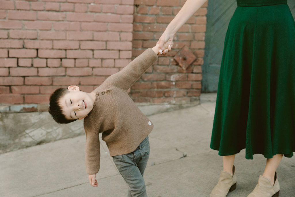 young boy holding mothers hand and leaning playfully