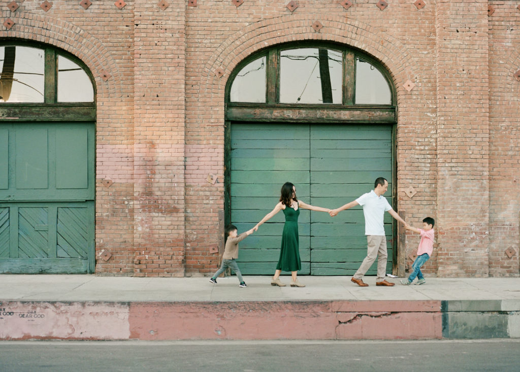 family of four holding hands in a row with brick building in background