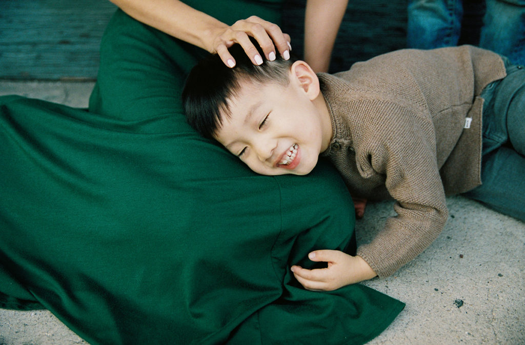 smiling boy pays on mothers lap with eyes closed