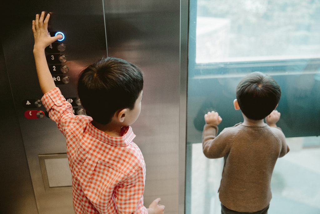 young boys riding in an elevator and pushing buttons