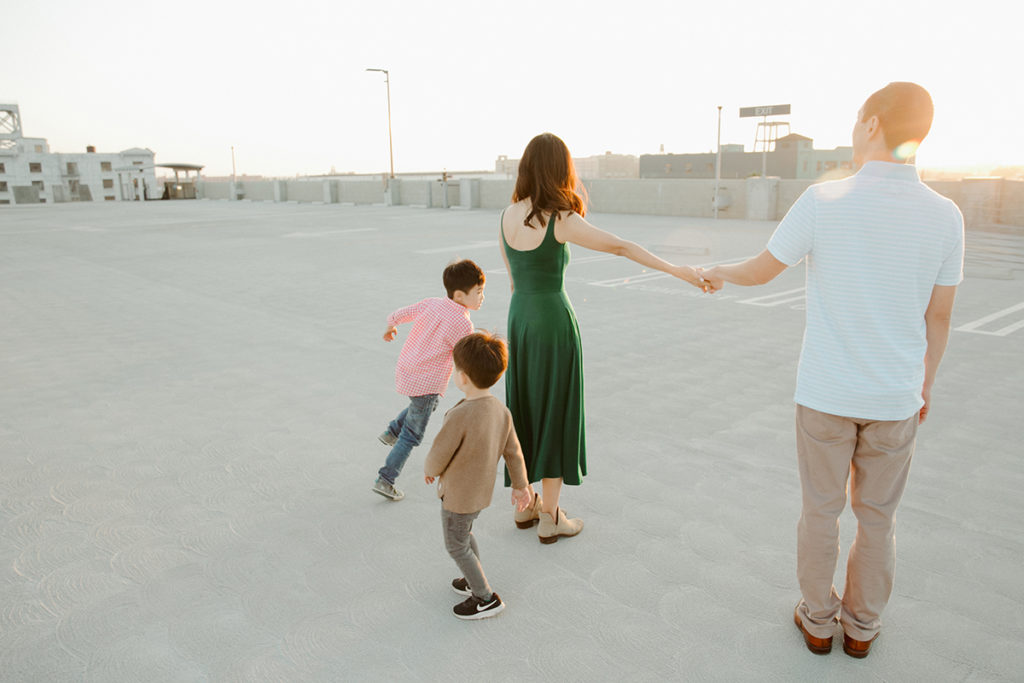 family on rooftop with magical lighting. Kids running around and parents holding hands