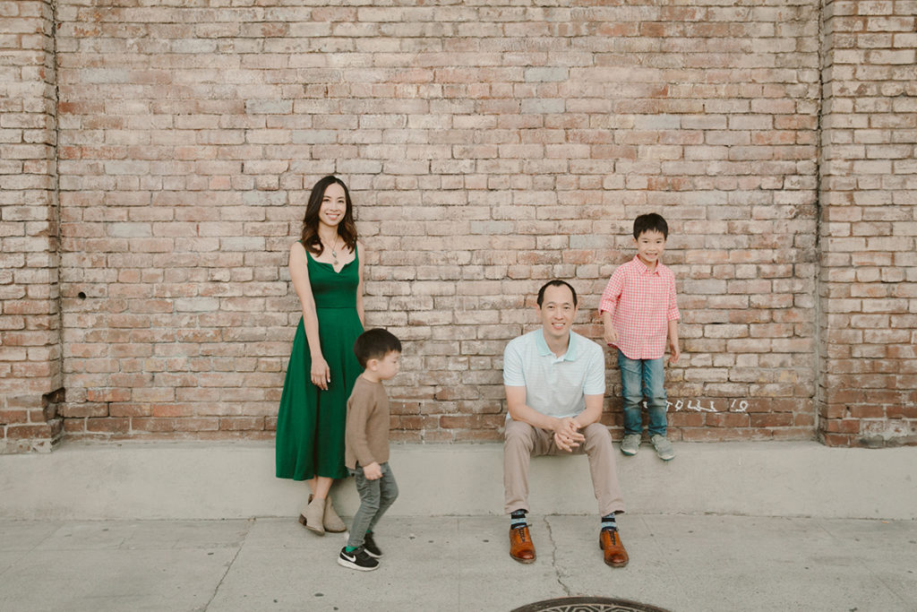 family of four with brick background, parents smiling at camera while kids play