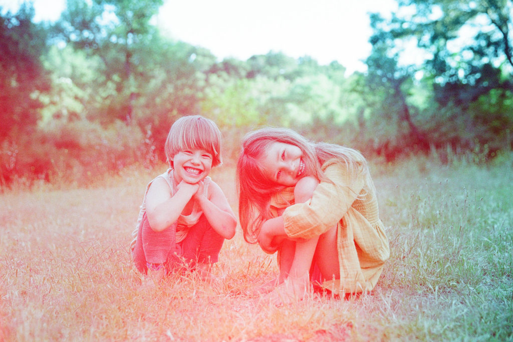 colorful film photo of smiling siblings